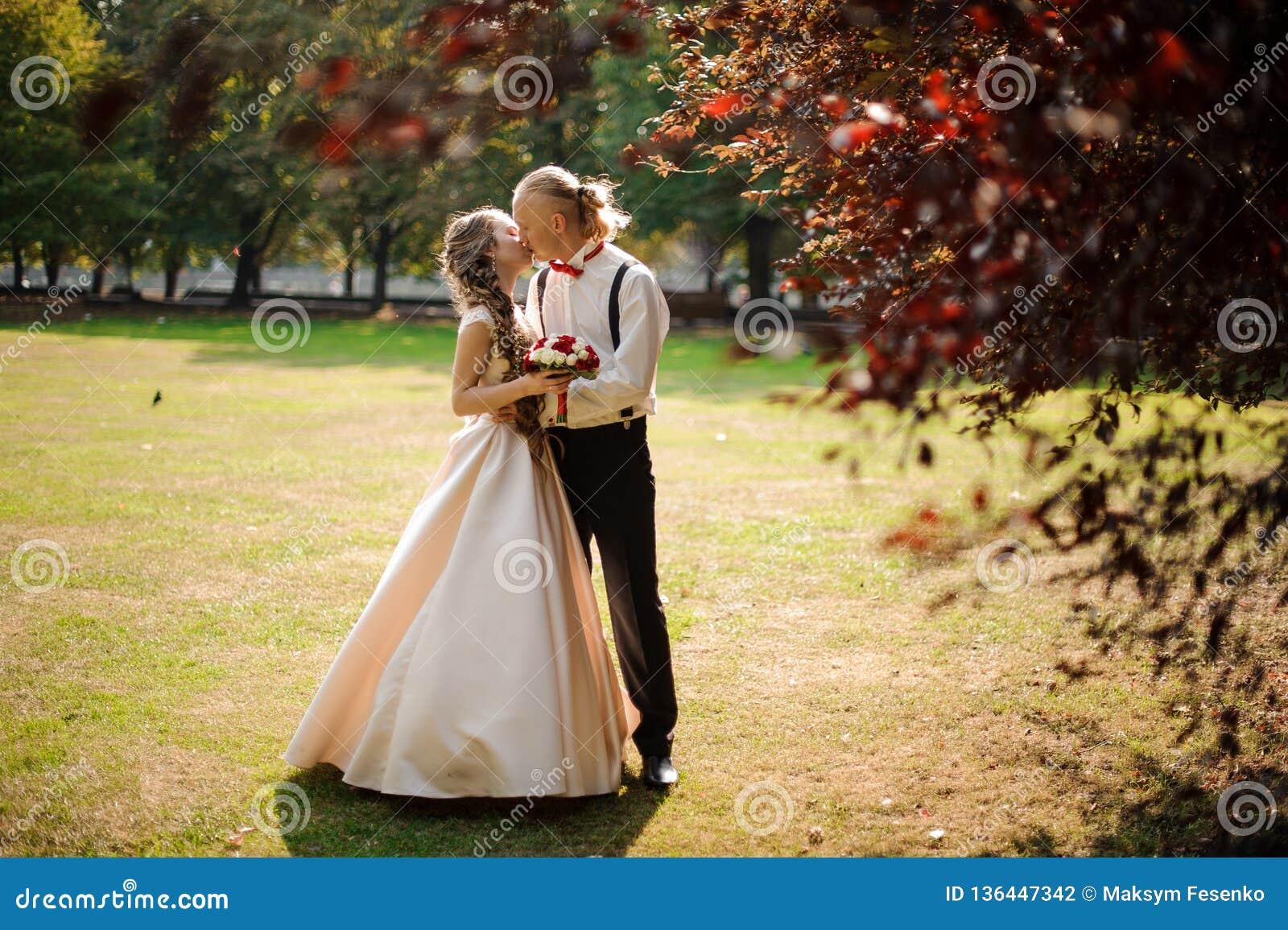 Ungt gift par som kysser på ett fält för grönt gräs med träd