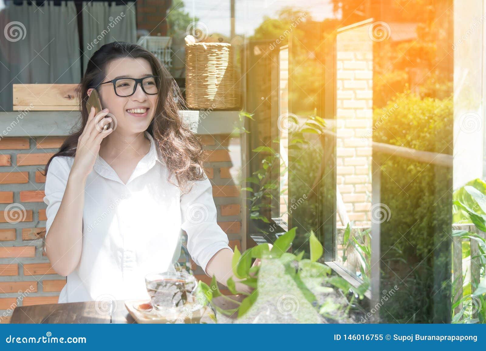 Ungt gladlynt leende f?r aff?rskvinna som sitter p? terrasskaf?t som tycker om online-kommunikation genom att anv?nda fri tr?dl?s