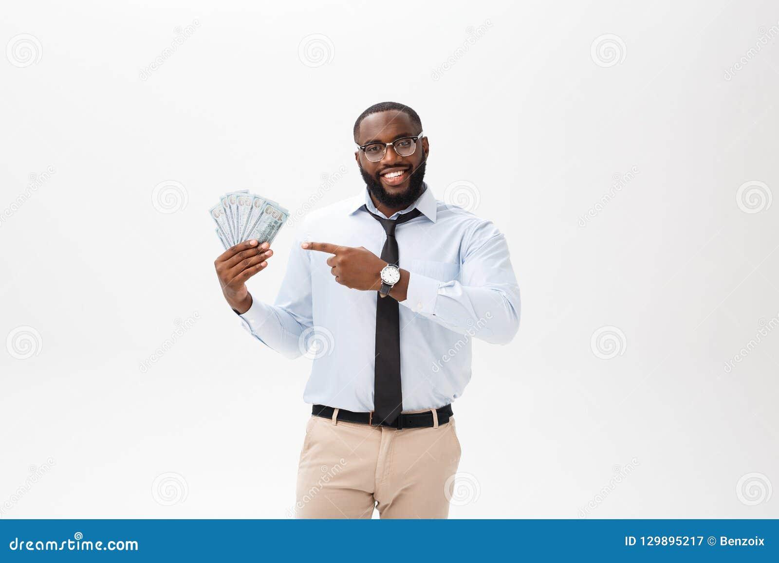 Ungt gladlynt svart affärsmaninnehav och peka på pengar som isoleras på vit