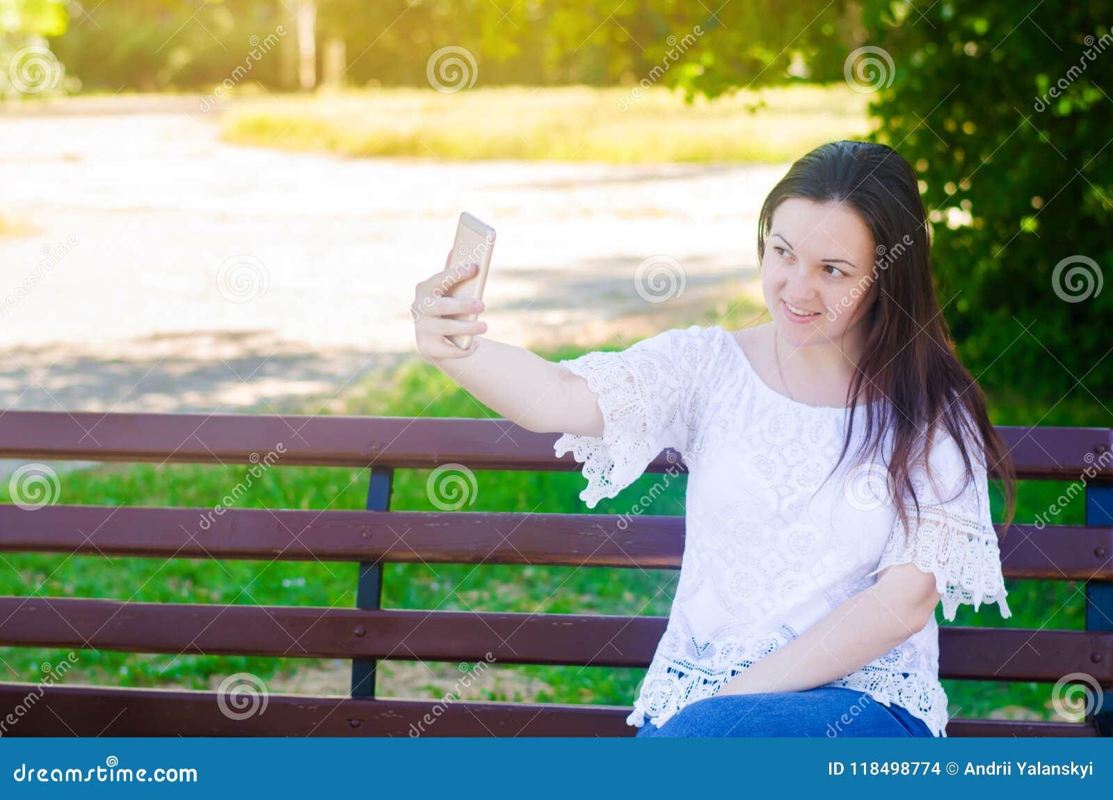 Ungt härligt europeiskt brunettflickasammanträde på en bänk och att ta en bild av henne, gör selfie i en stad att parkera i ett s