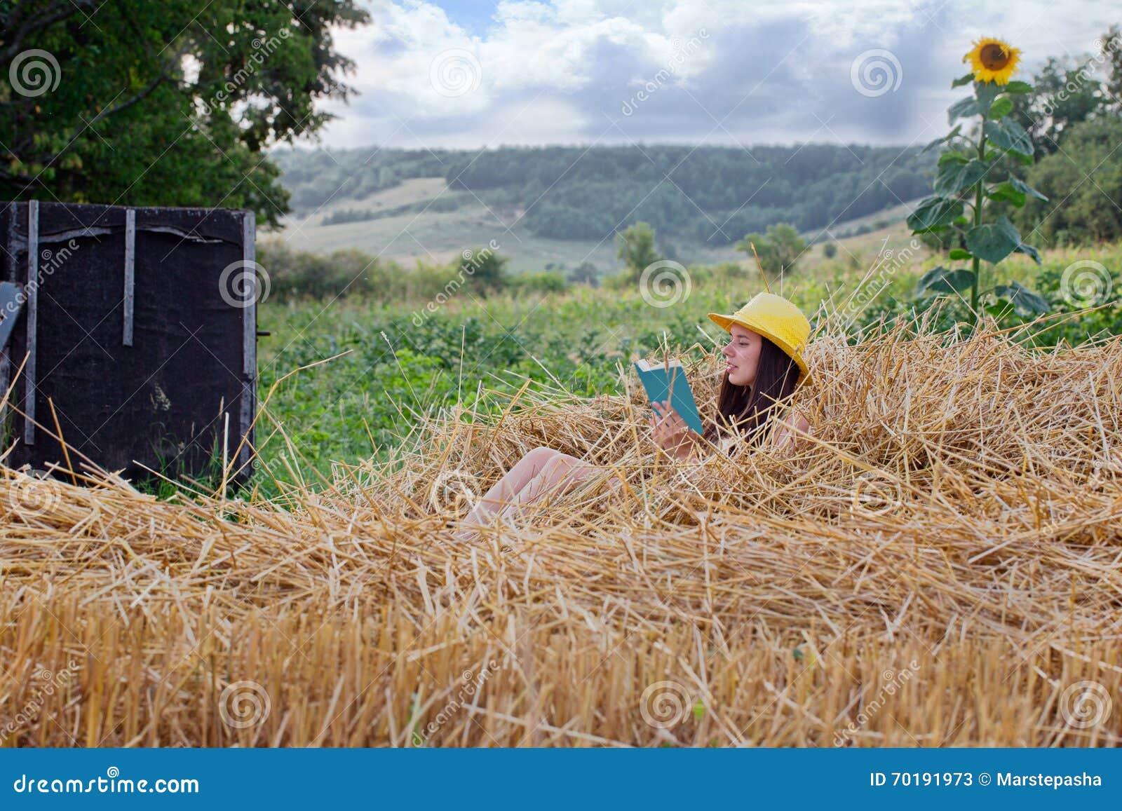 Ungt härligt flickasammanträde på sugrör och läsning en bok