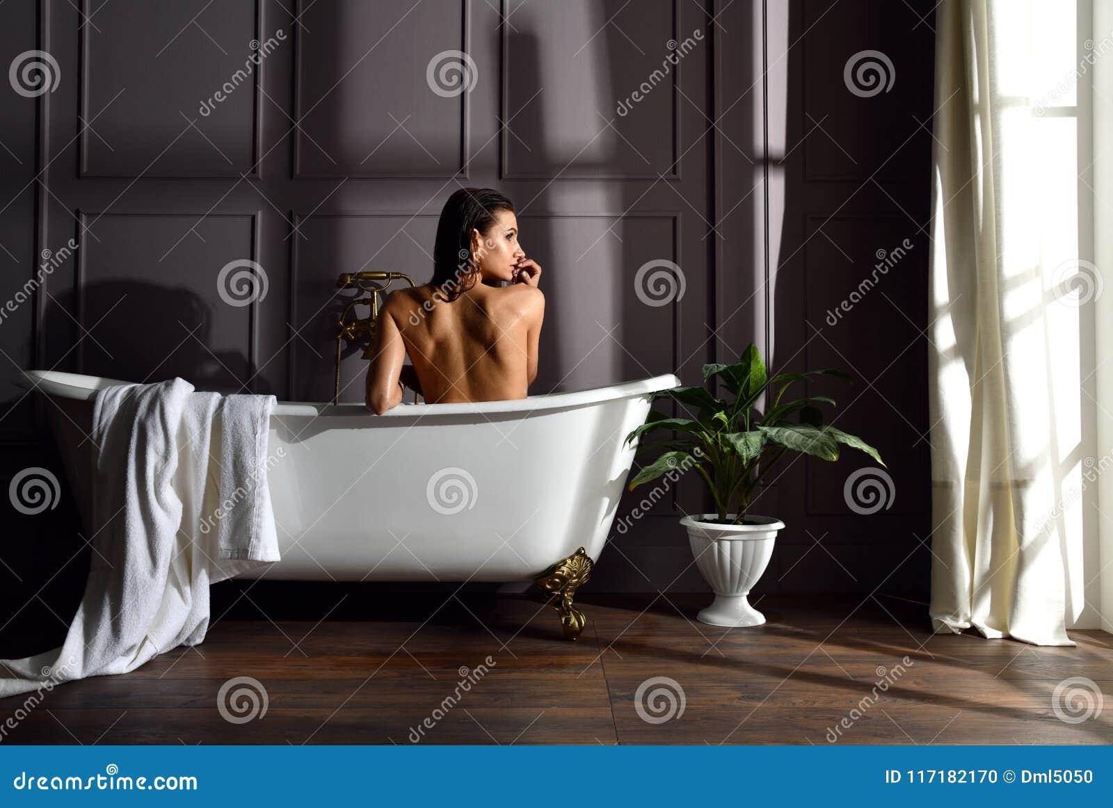 Ungt härligt kvinnasammanträde i badrum nära det dyra badkarbadet som ser hörnet på mörker