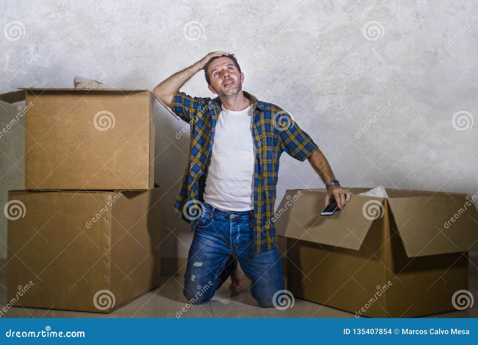 Ungt hemmastatt golv för lycklig och upphetsad man som tycker om packa upp kartonger som bara flyttar sig till nytt le för lägenh
