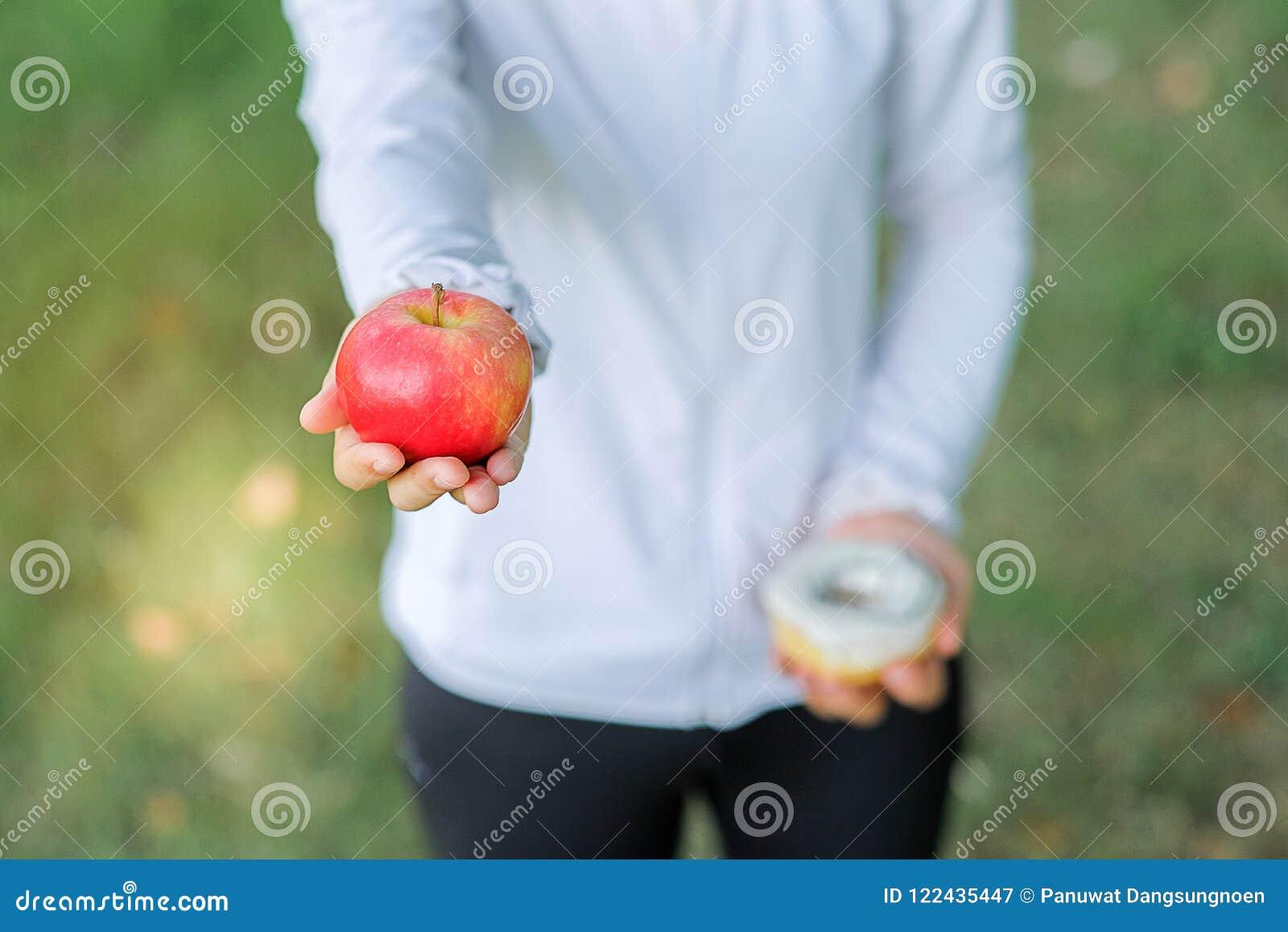 Ungt konditionkvinnainnehav i händer rött äpple och munk