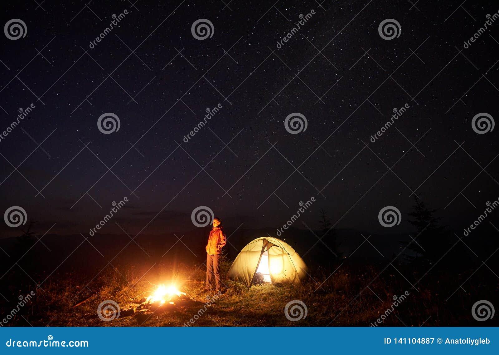 Ungt kvinnligt turist- stående near upplyst tält som campar i berg på natten under stjärnklar himmel