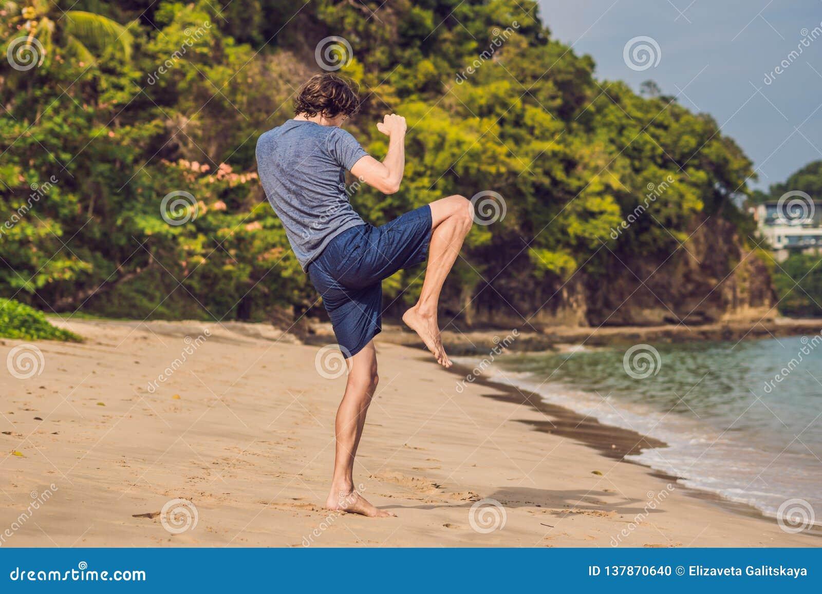 Ungt manligt utarbeta på stranden, sportig man som gör övningar