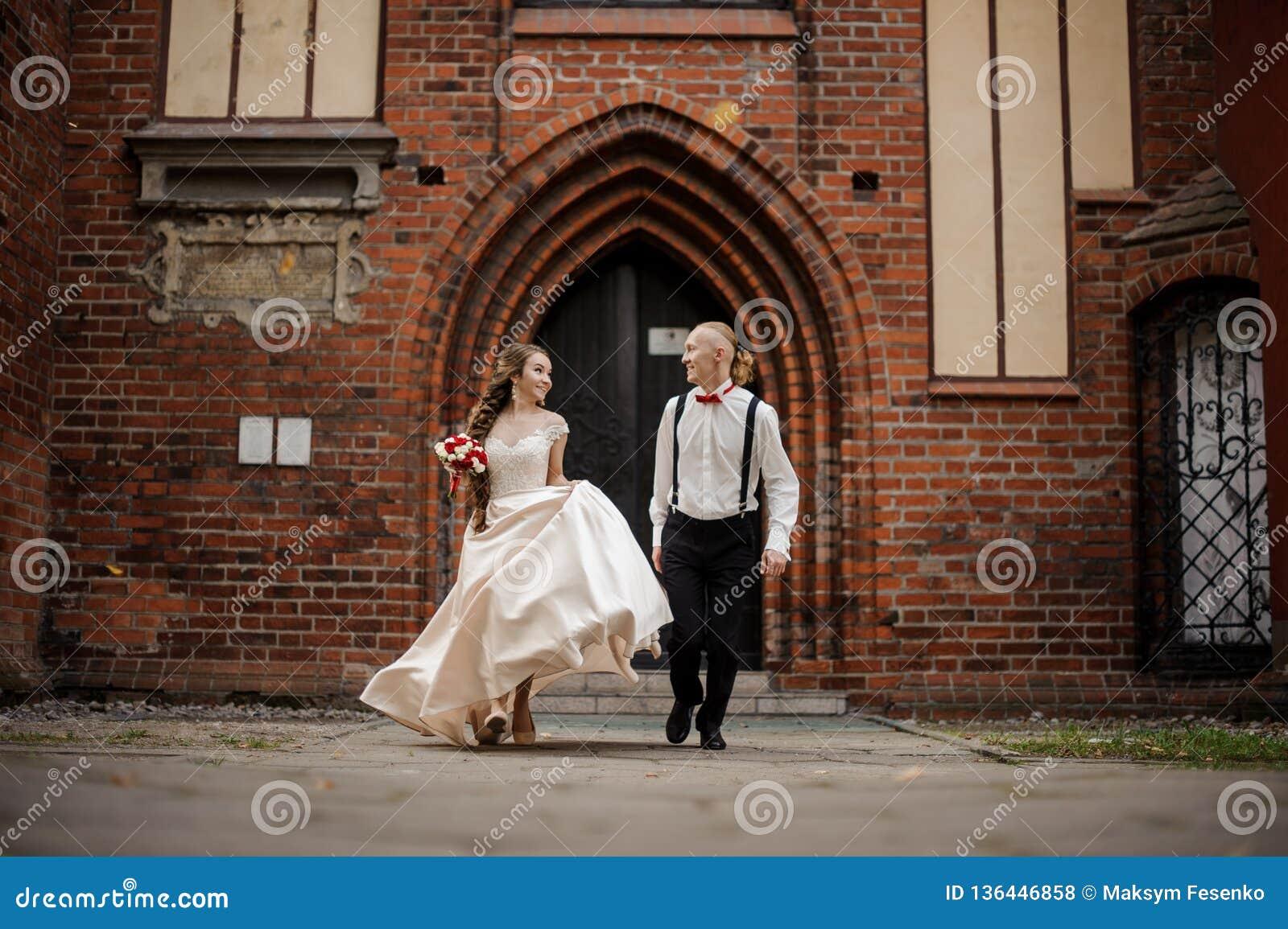 Ungt och lyckligt gift par som går i en gård av gammal byggnad för röd tegelsten för tappning