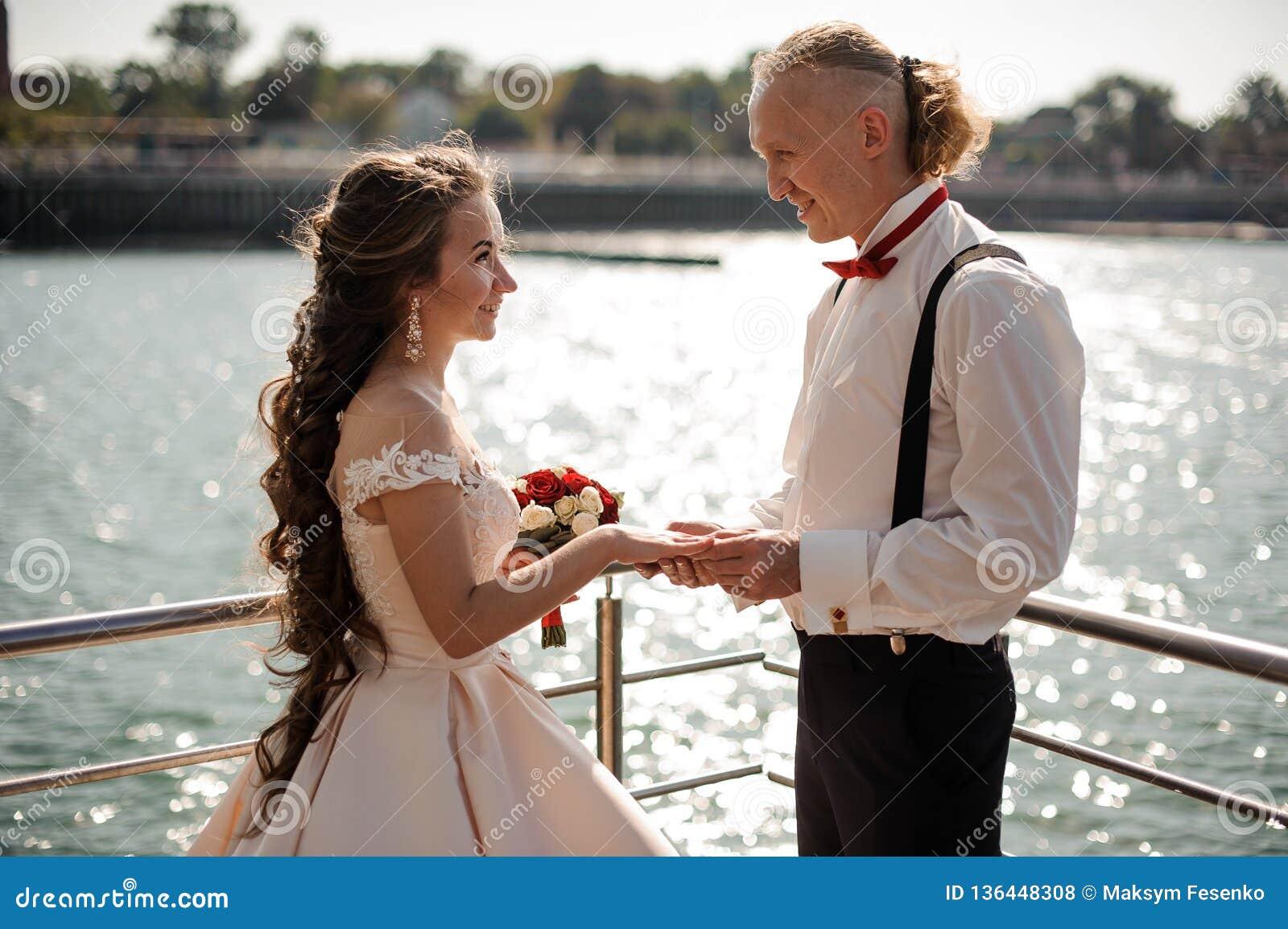 Ungt och lyckligt gift par som utbyter vigselringarna
