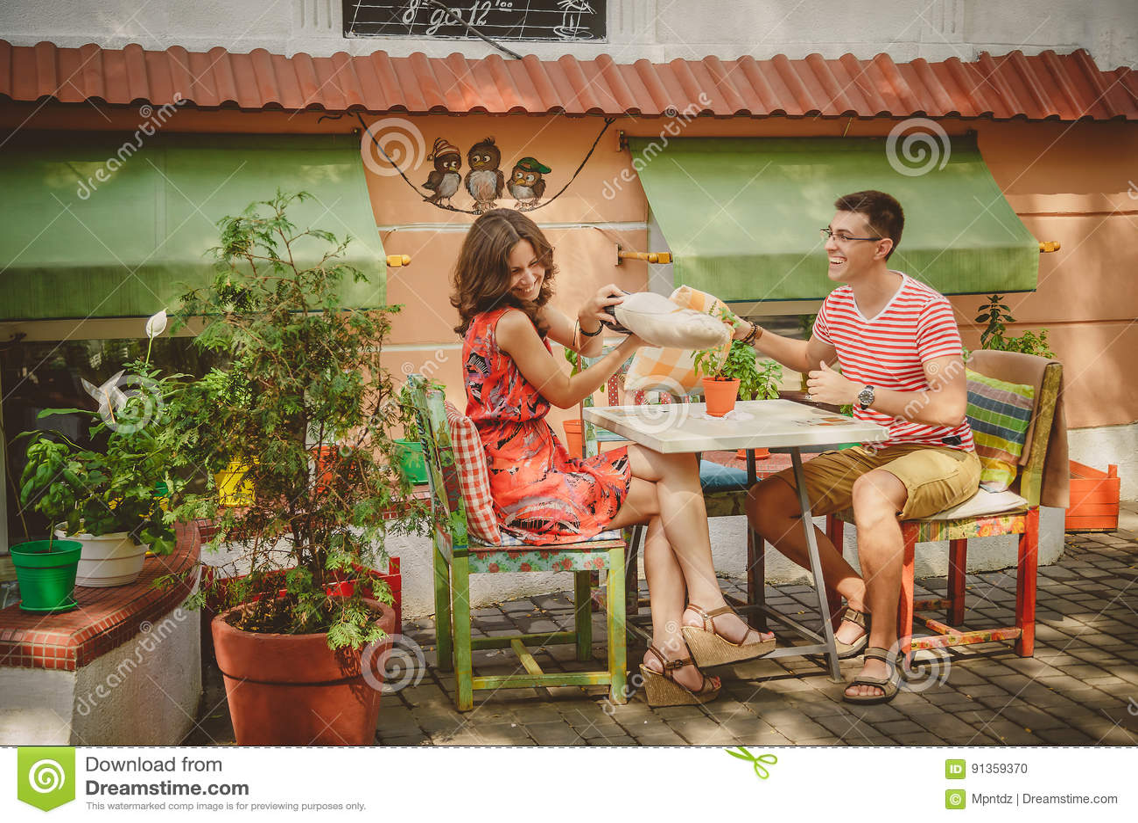 Ungt roligt lyckligt älska parsammanträde på det frilufts- kafét för gata och stridighet med kuddar utomhus Kuddekamp