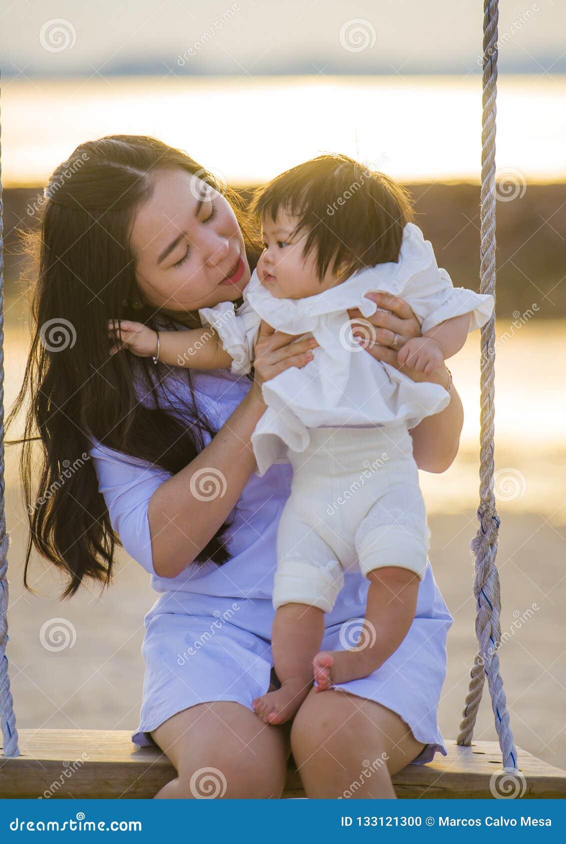 Ungt sött och lyckligt asiatiskt kinesiskt rymma för kvinna behandla som ett barn flickan som tillsammans svänger på strandgunga