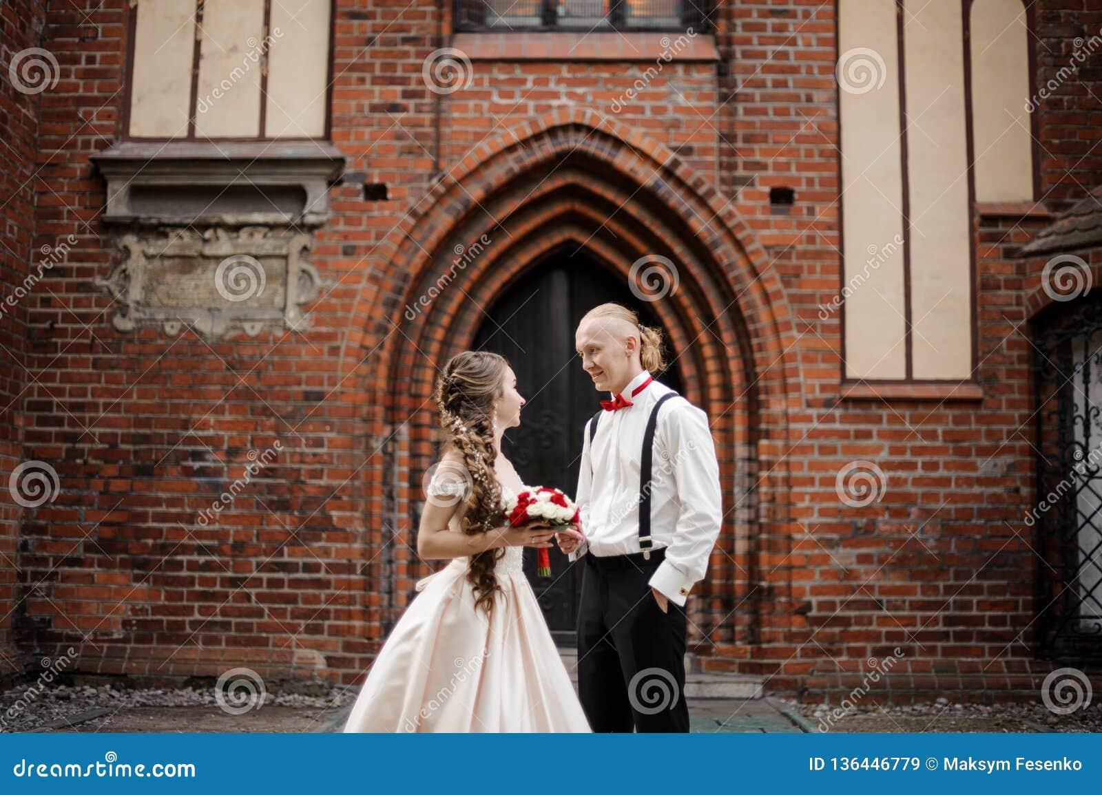Ungt stilfullt gift paranseende och le i bakgrunden av den gamla byggande bågen