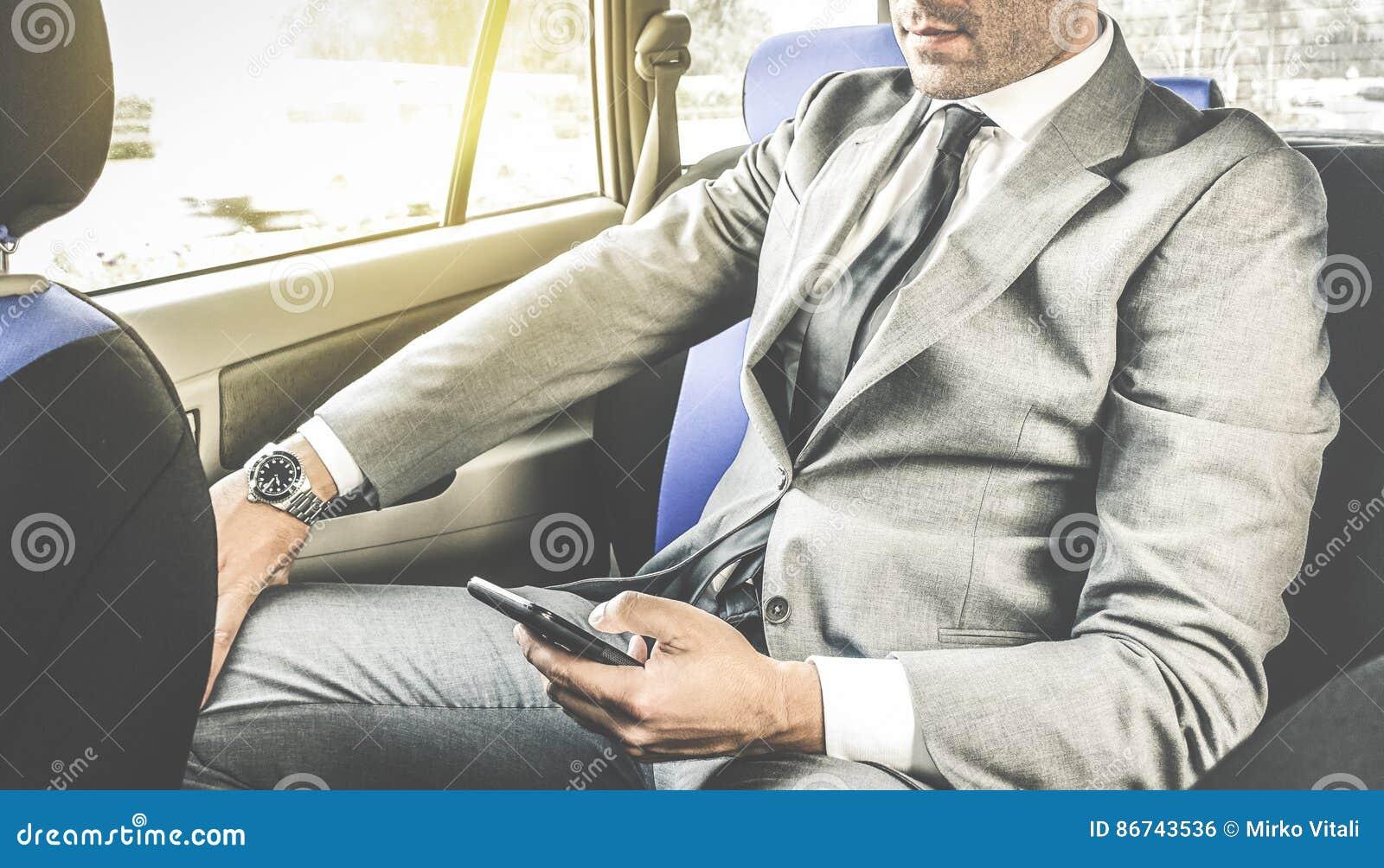 Ungt stiligt affärsmansammanträde i taxitaxi med telefonen