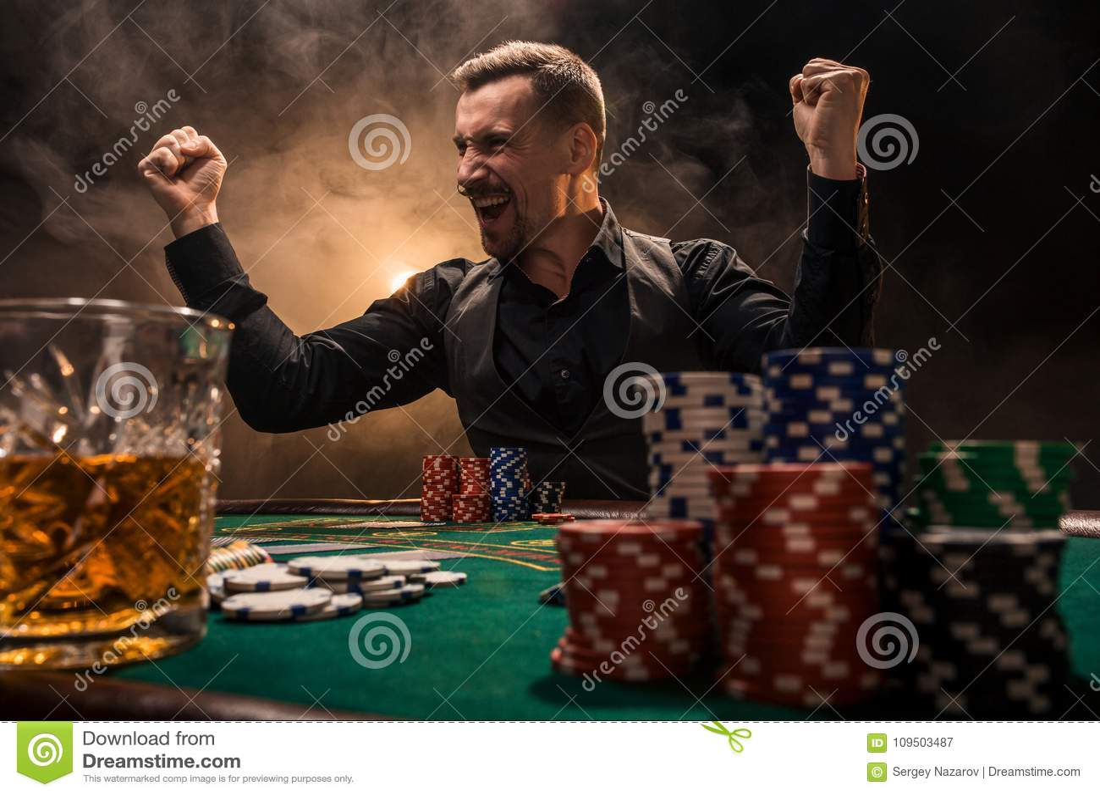Ungt stiligt mansammanträde bak pokertabellen med kort och chiper