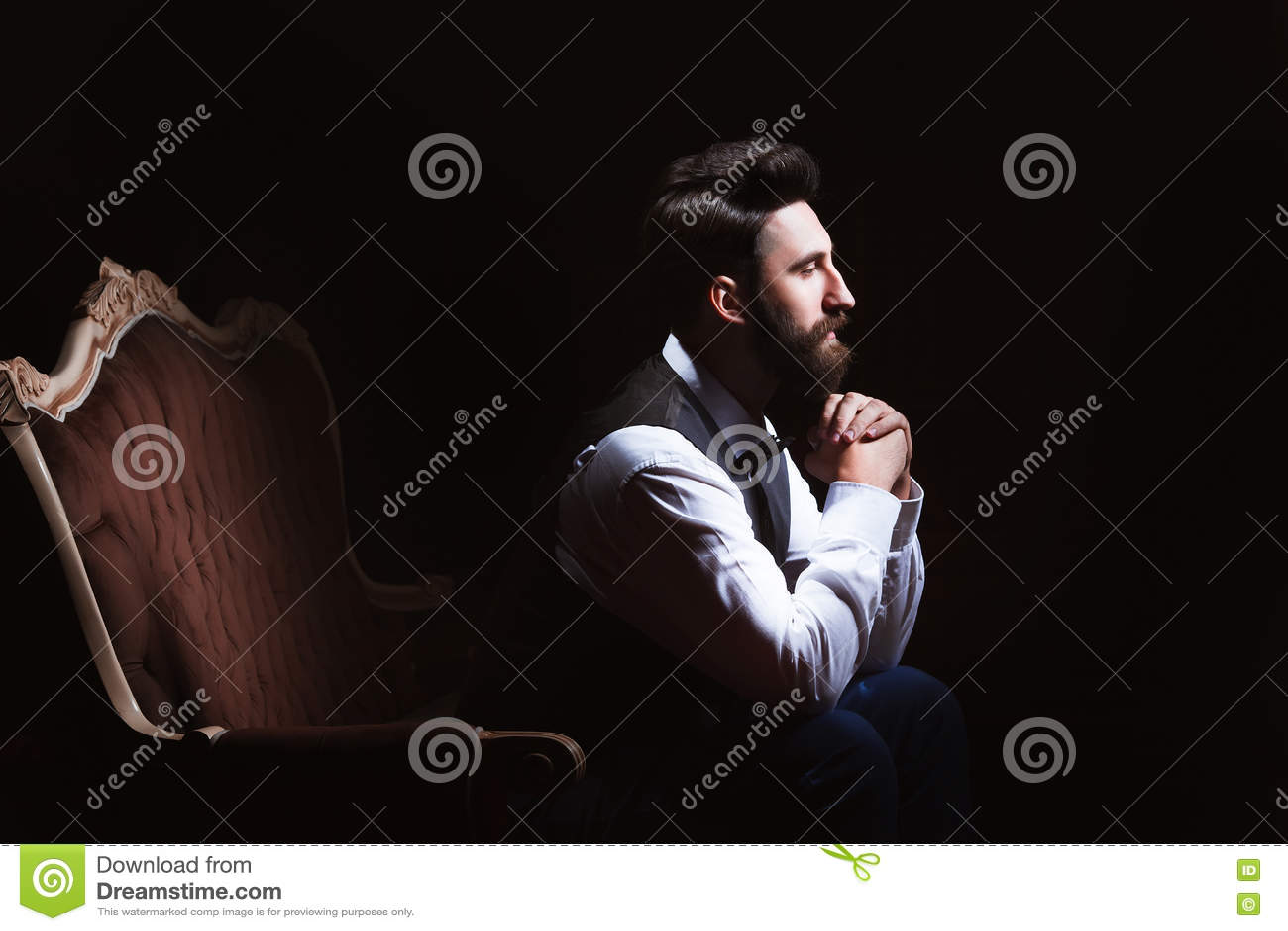 Ungt stiligt skäggigt caucasian mansammanträde på tappningsoffan Göra perfekt hud och frisyren Bärande väst, vit skjorta