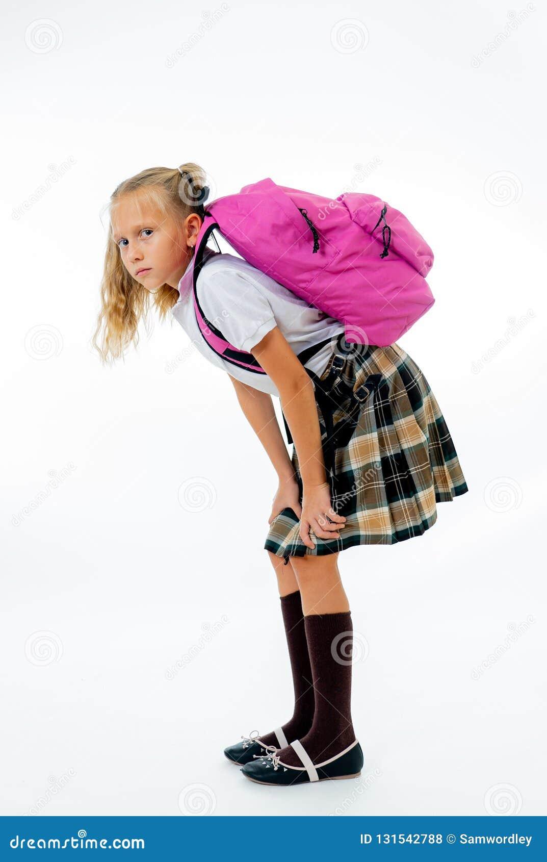 Ungt trött och ledset gulligt skolaflickaanseende med en stor tung skolapåse på hennes baksida på en vit bakgrund för isolat för