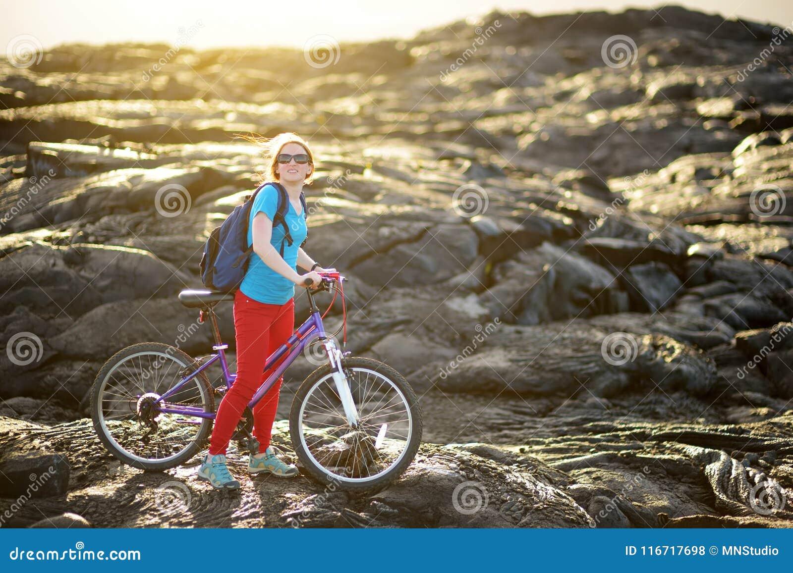 Ungt turist- cykla på lavafält på Hawaii Kvinnlig fotvandrare som heading till lava som beskådar område på Kalapana på hennes cyk