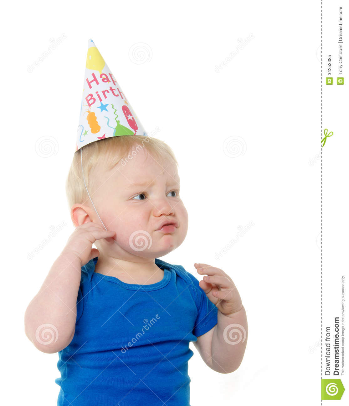 Cute 18 Month Old Baby Boy With Blond Hair And Blue Shirt Crying While Wearing A Happy Birthday Hat On White Background