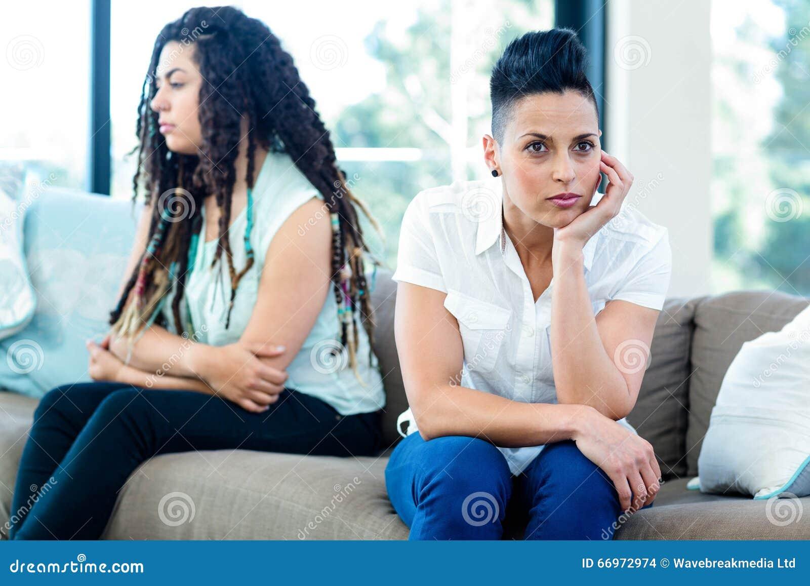 Unhappy lesbian couple sitting on sofa