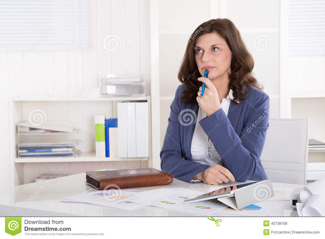 Unhappy older pensive business woman sitting at desk.