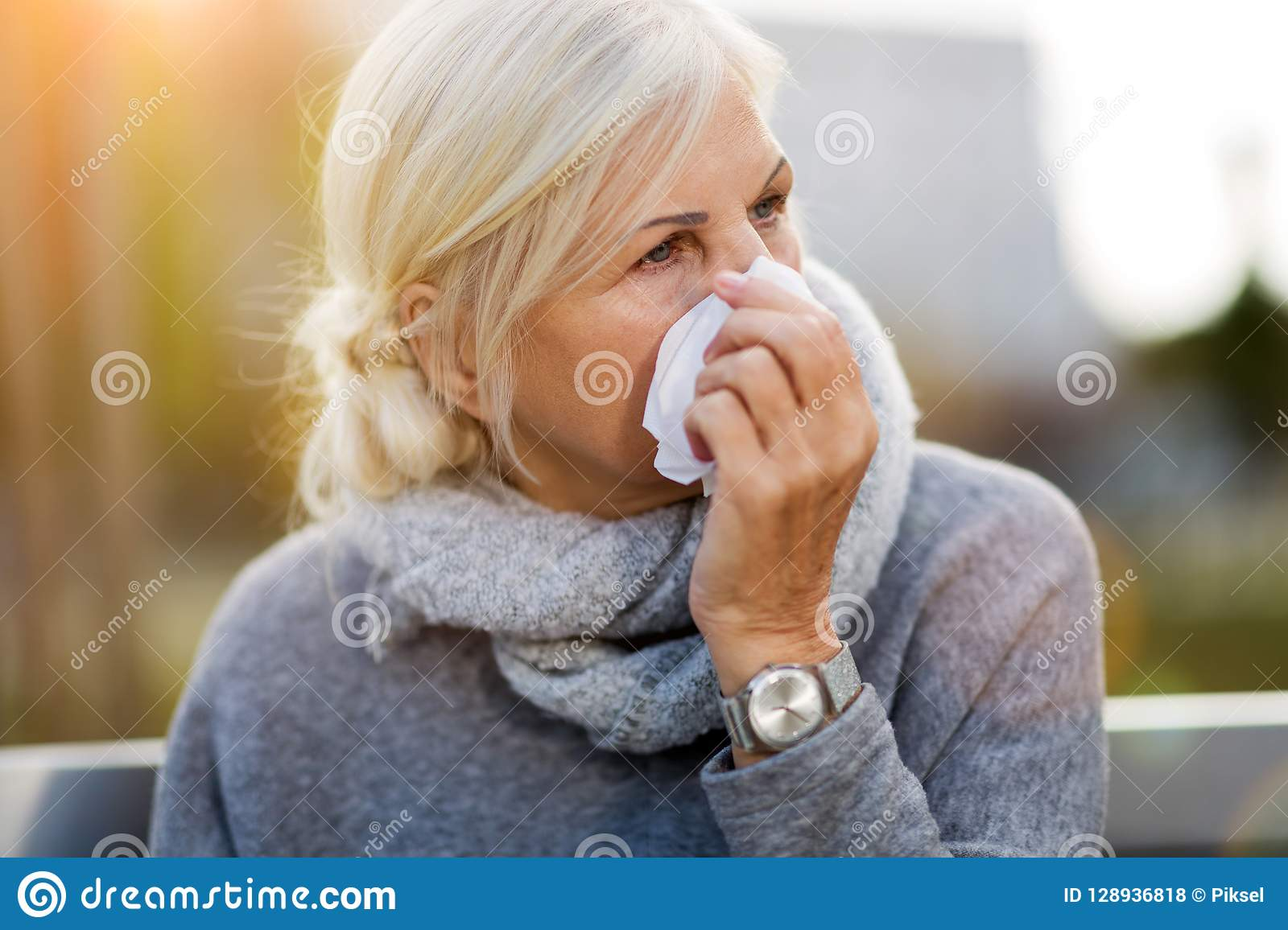 Weeping old woman wipes her eyes with tissue