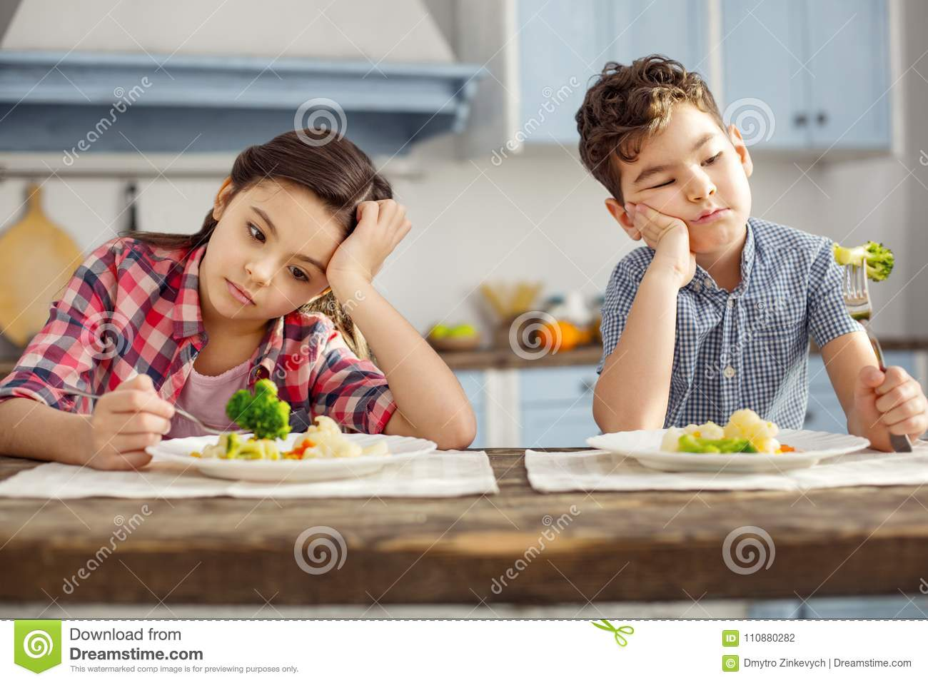 Unhappy siblings looking sadly at the vegetables
