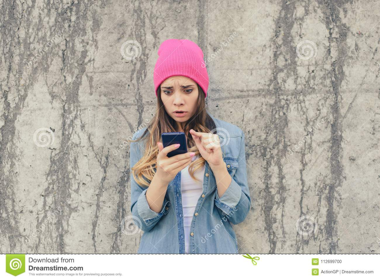 Unhappy surprised sad jealous woman reading sms on her boyfriend`s mobile phone. Cell cellphone mobile phone telephone smartphone