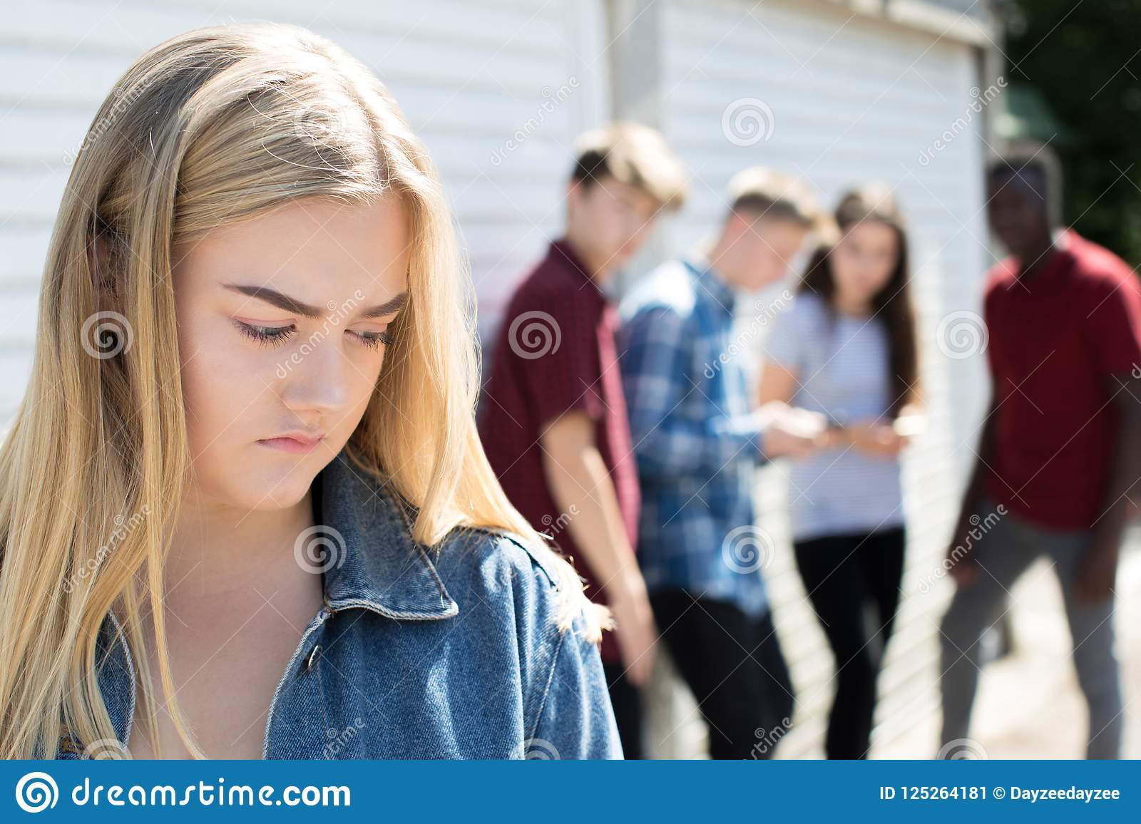 Unhappy Teenage Girl Being Gossiped About By Peers