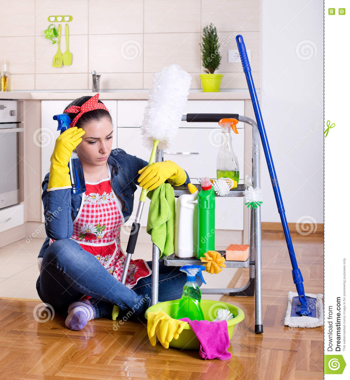 Kitchen Cleaning: Unhappy Woman With Cleaning Supplies In The Kitchen Stock