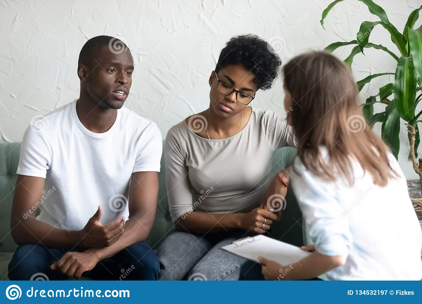 Unhappy young African American couple visiting psychologist
