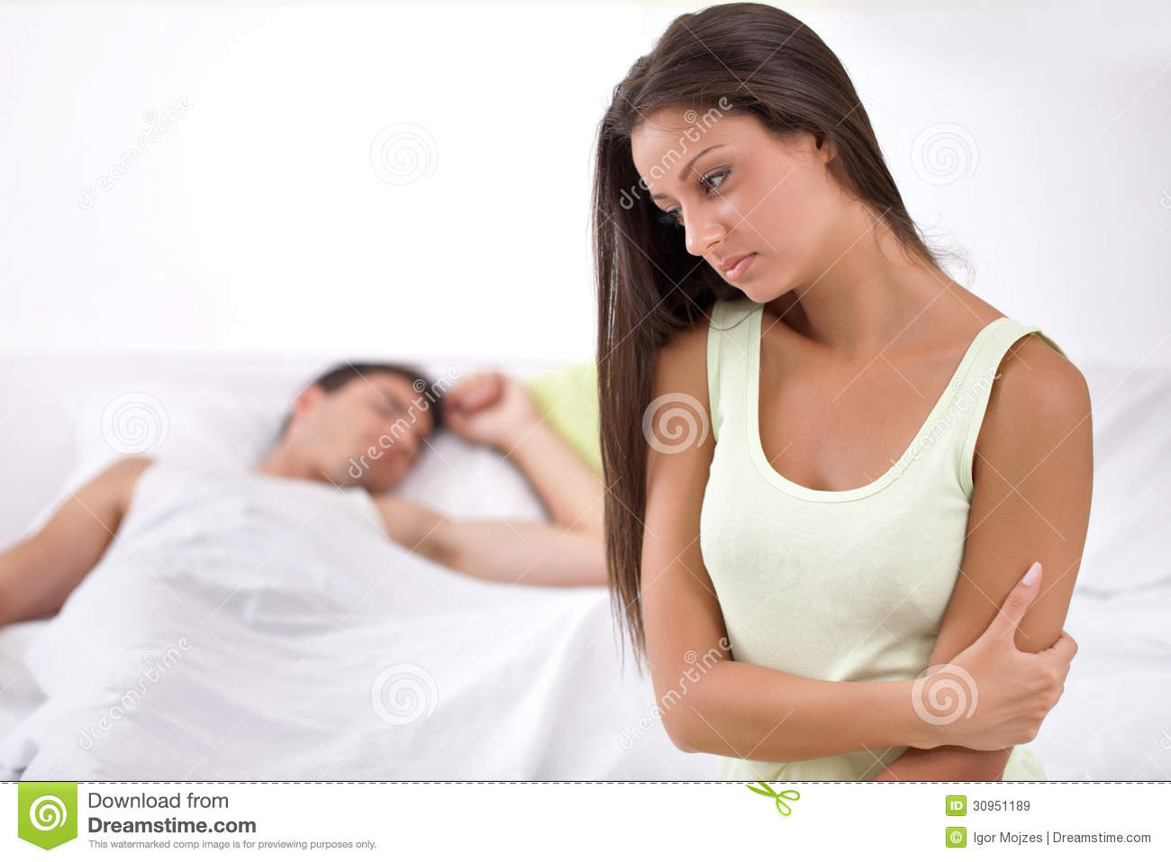 Unhappy young woman in bedroom