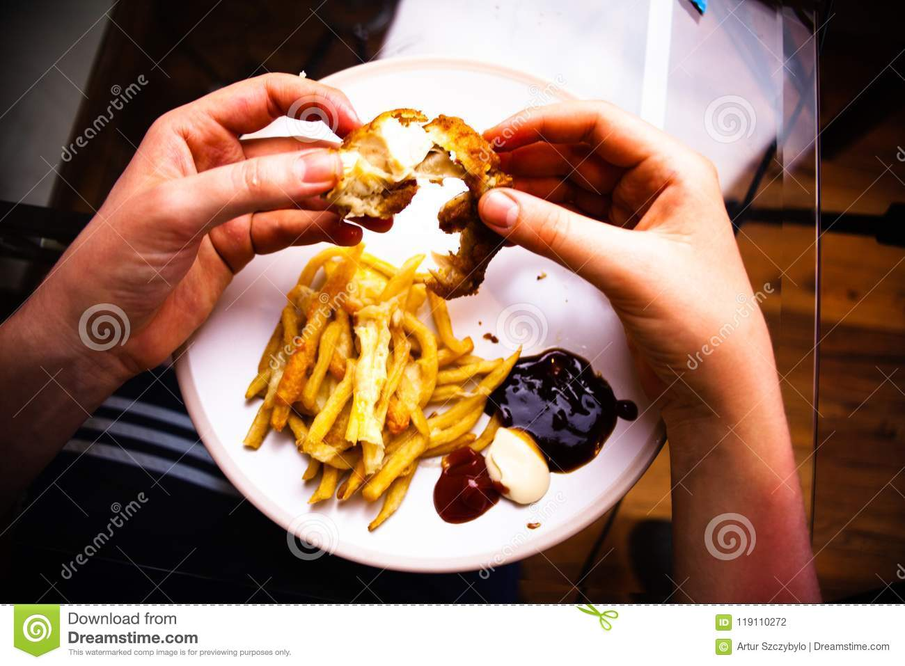 Unhealthy eating fast food concept. Man is holding chicken fried wings in his hands. Eating meal with hands. Delicious food prepar