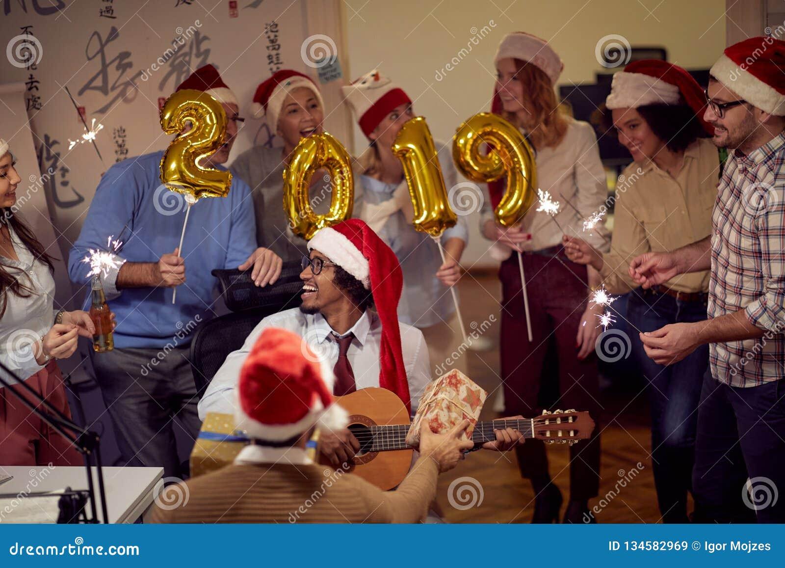 Unidad de negocio sonriente que se divierte en la celebración del Año Nuevo
