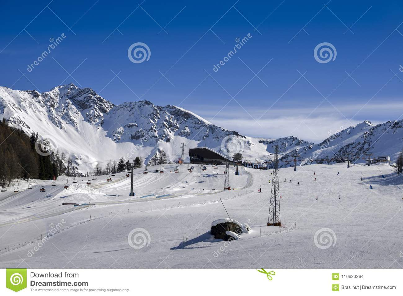 unidentifiable skiers at ski resort in pila, valle d`aosta, italy