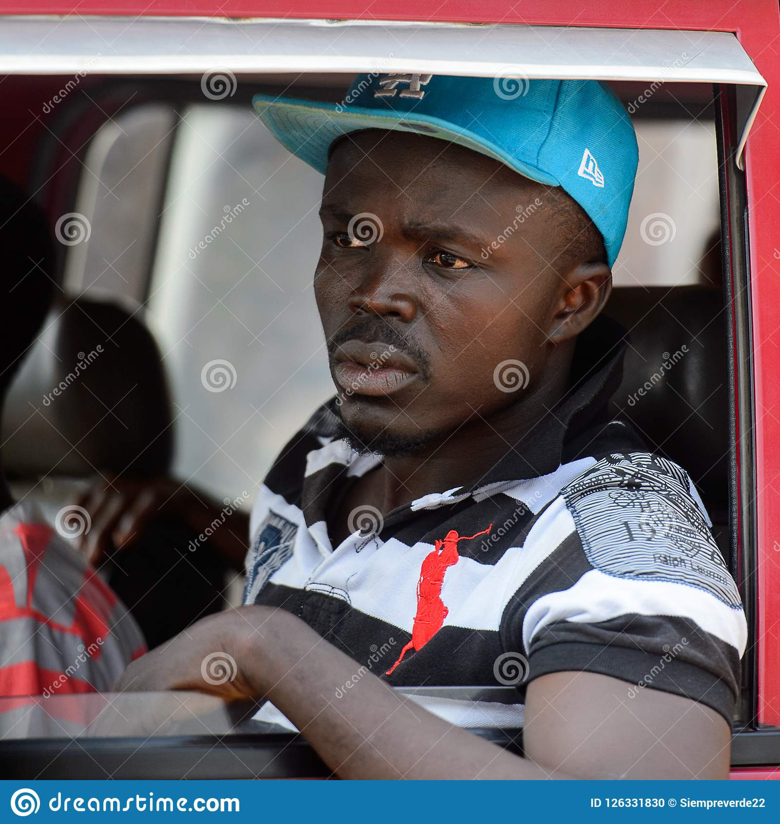 Unidentified Ghanaian man looks out of the red car s window in