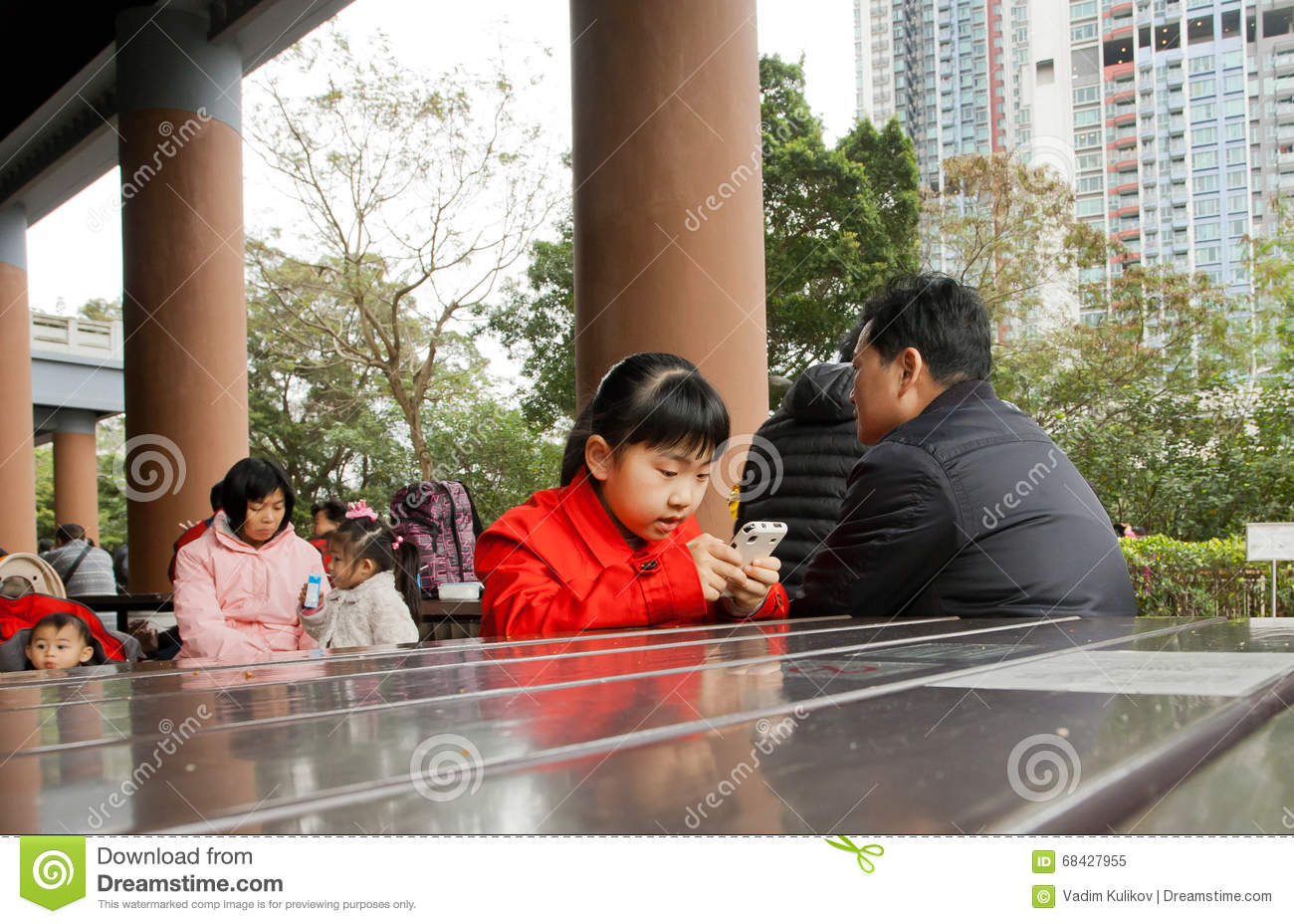 Unidentified girl playing mobile game on smartphone near for Smartphone da hong kong