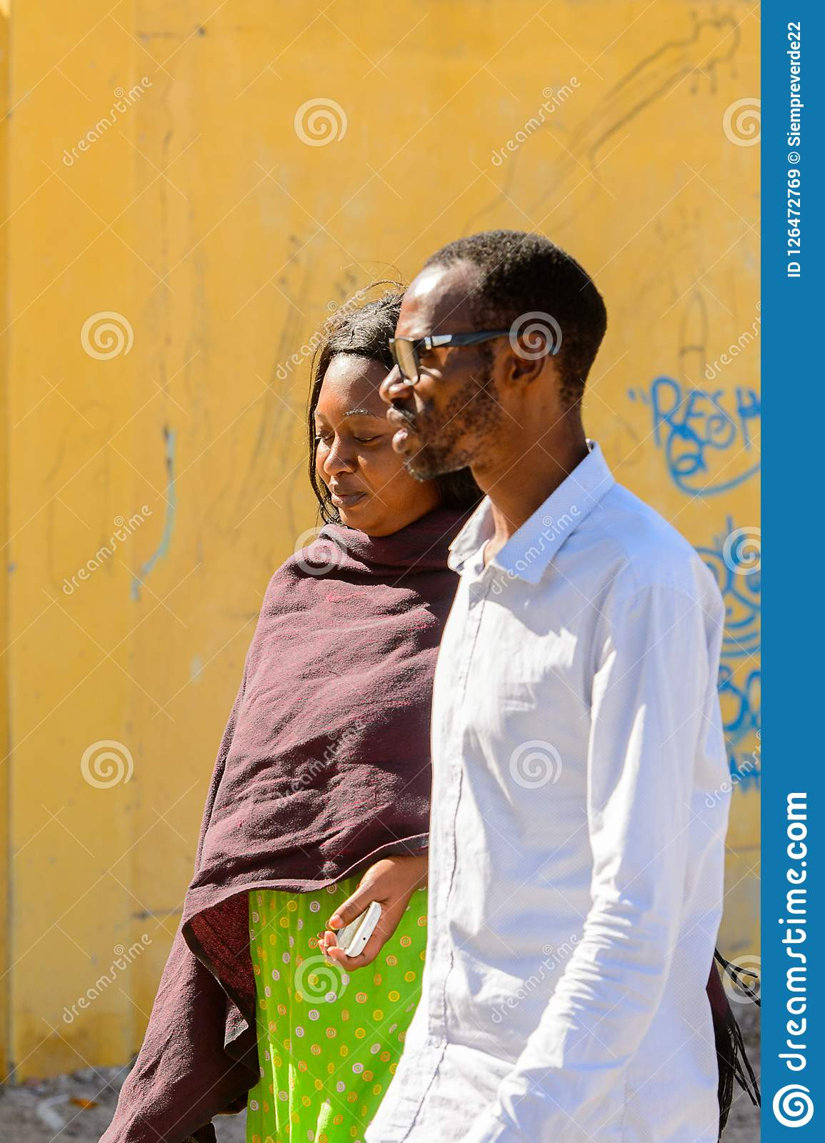 Unidentified Senegalese man and woman walk along the street in