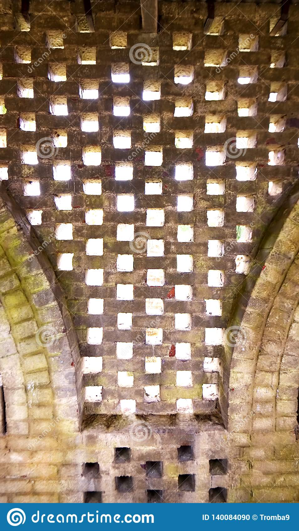 An abstract pattern created by bricks in an old wall.
