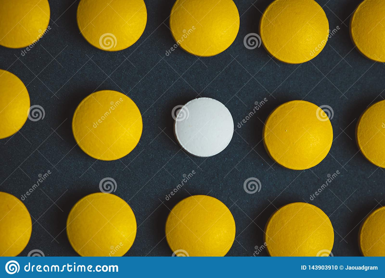 Unique white medicine pill among many yellow ones. Stand out of a crowd, individuality and difference concept. Leadership concept