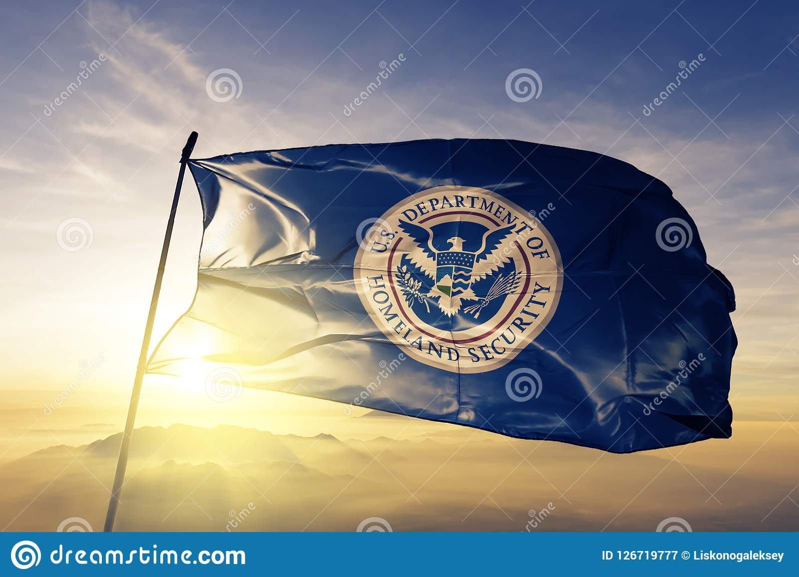 United States Department of Homeland Security flag textile cloth fabric waving on the top sunrise mist fog