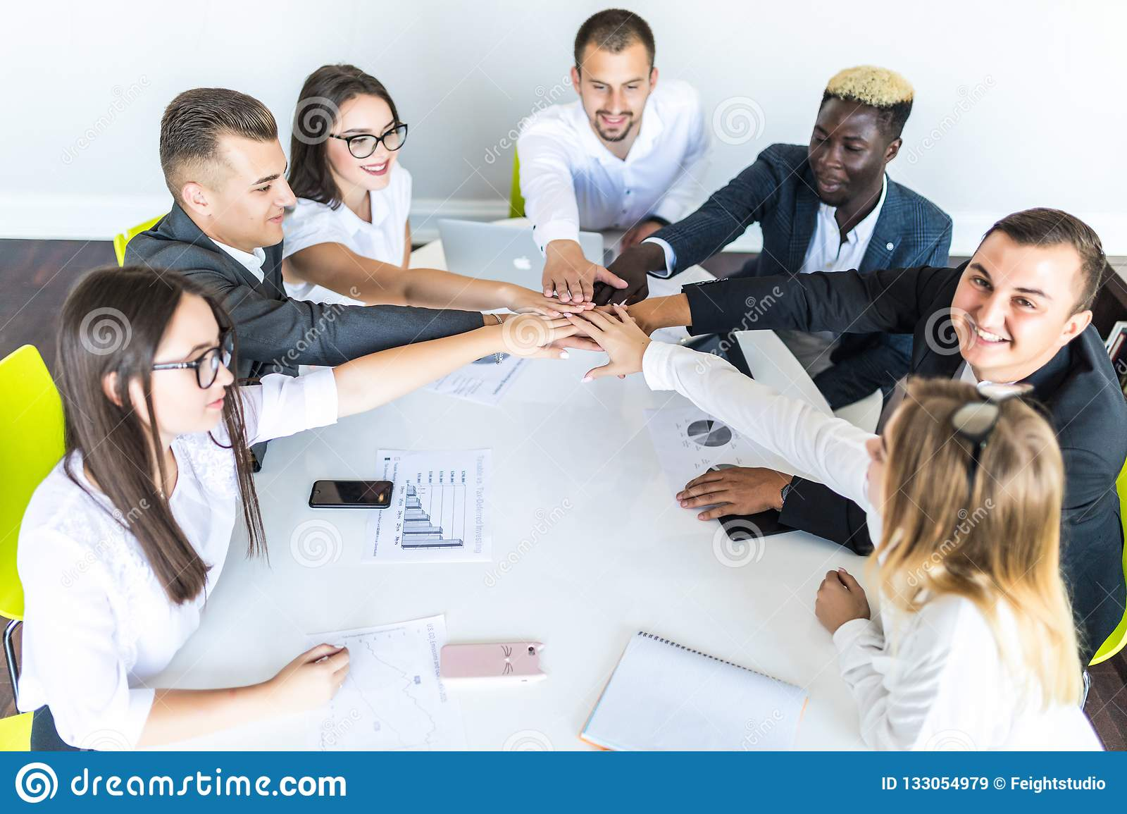 Unity concept. Close-up of multi ethnic people holding hands together while sitting around the desk