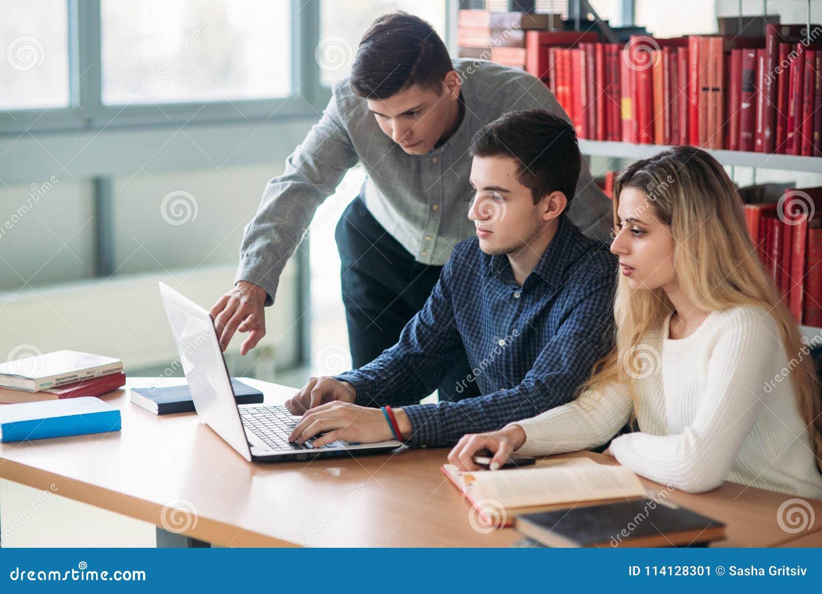 Universitaire studenten die samen bij lijst met boeken en laptop zitten Gelukkige jongeren die groepsstudie in bibliotheek doen