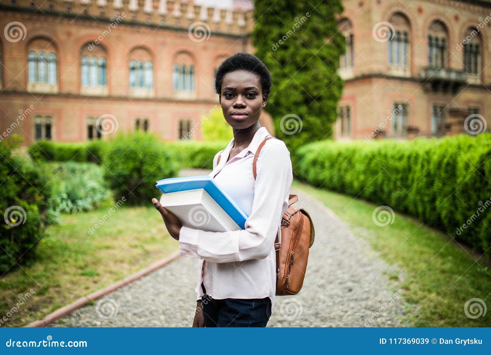 Universitetsområdeliv Kvinnlig högskolestudent för ung attraktiv afrikansk amerikan på universitetsområde