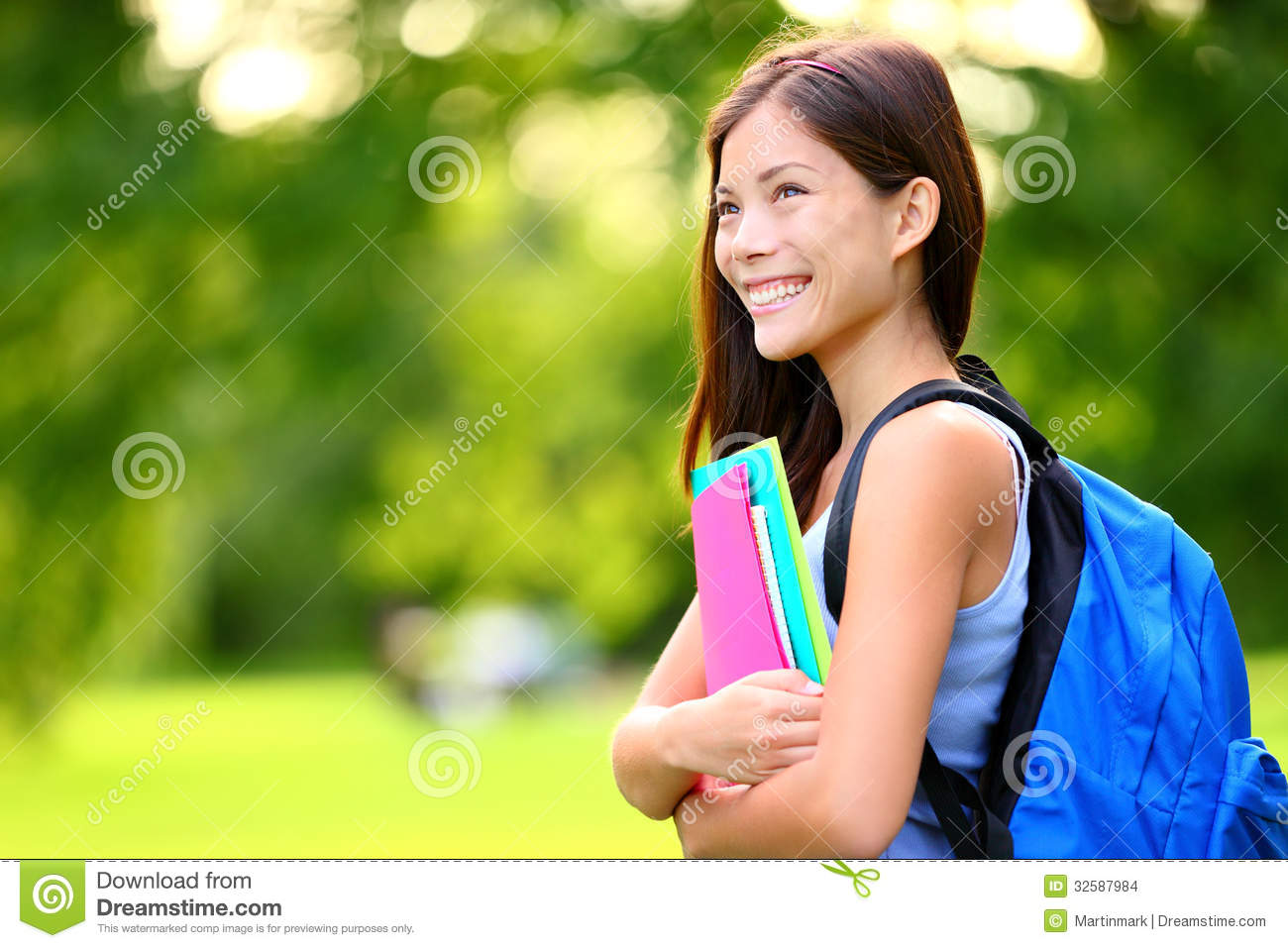 University / college student girl looking happy smiling with book or ...
