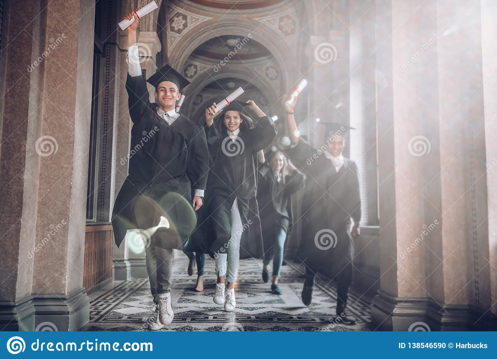 University was the best years of their lives!Group of smiling university students holding their diplomas and running after being