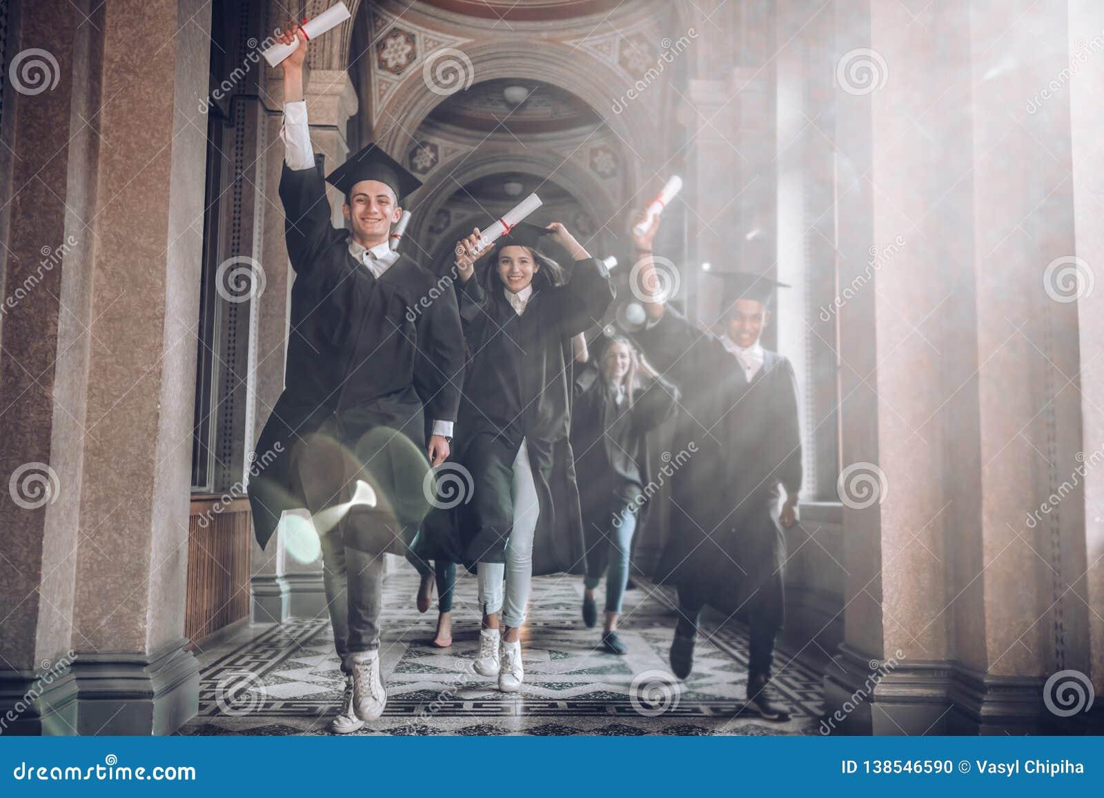 Uniwersytet był najlepszy rok ich życia! Grupa uśmiechnięci student uniwersytetu trzyma ich bieg i dyplomy po być