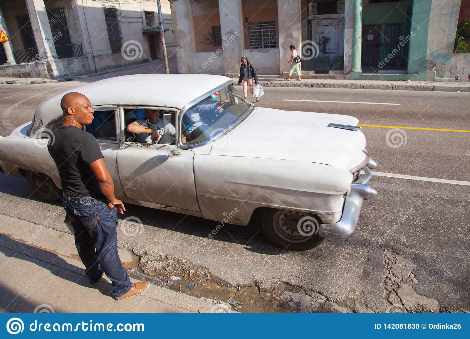 Unknown Cuban near a retro taxi on the streets of a dangerous area of Serrra