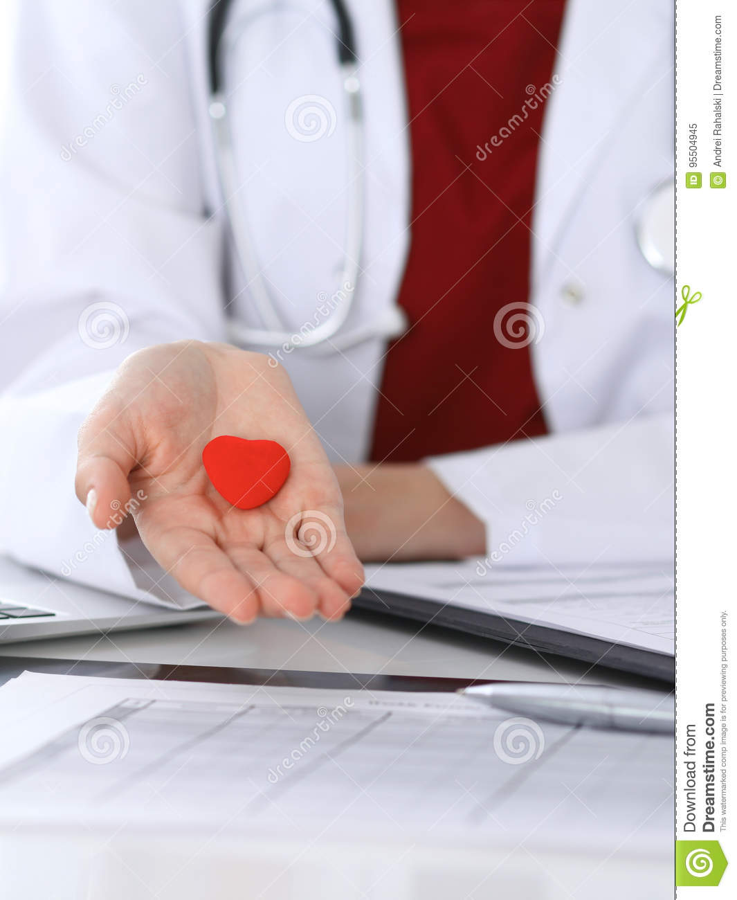 Unknown female doctor with stethoscope holding heart