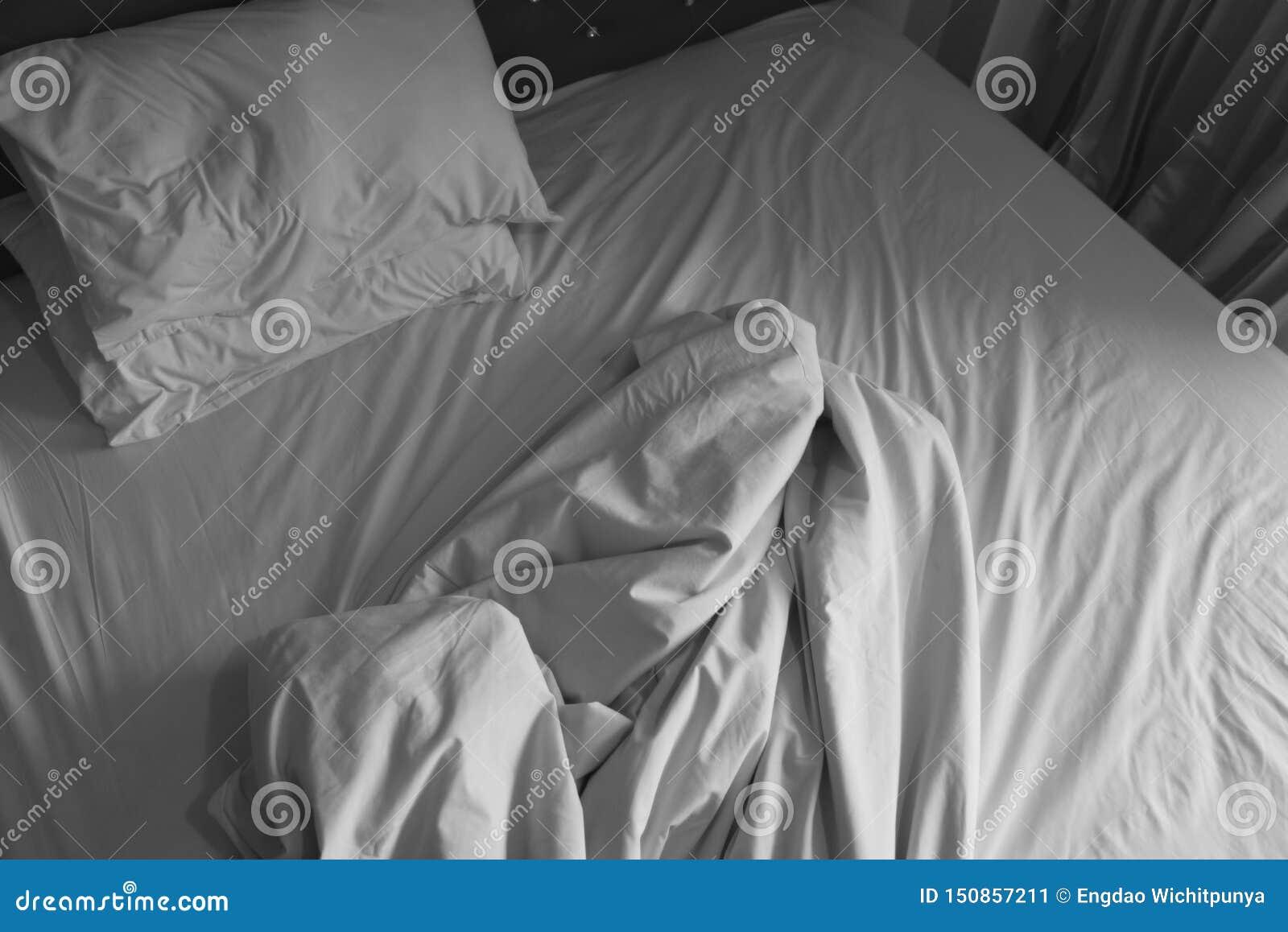 Unmade łóżkowy prześcieradło zagniecenia i poduszki biała koc w sypialni po sen na odgórnym widoku - Marszcząca tkanina