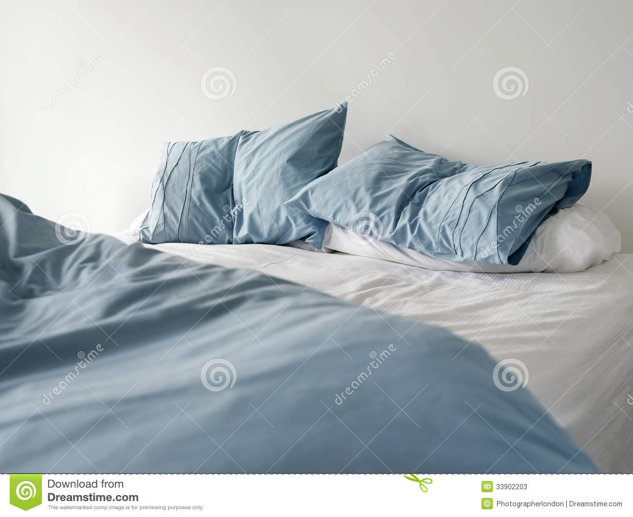 Rumpled bed sheet - Unmade Bed With Crumpled Blue Bed Linens Stock Photos