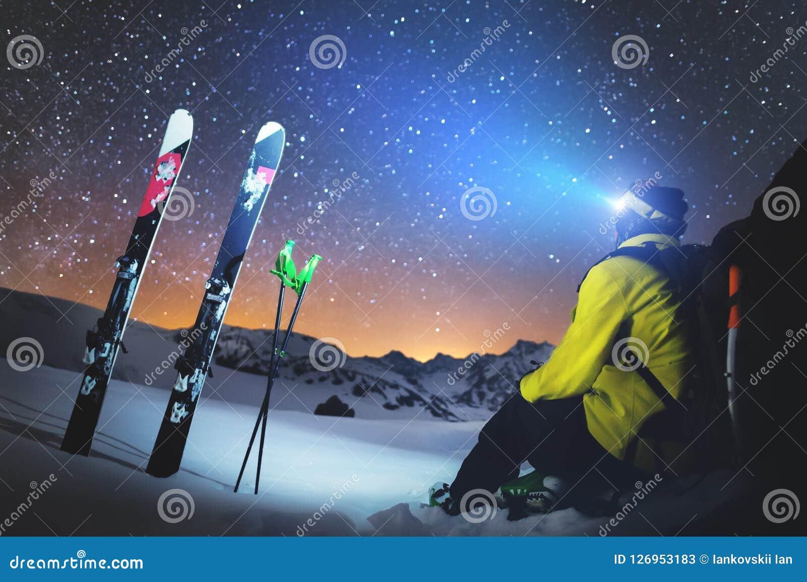Uno sciatore si siede ad una pietra nelle montagne alla notte contro un cielo stellato accanto agli sci ed ai bastoni Il concetto